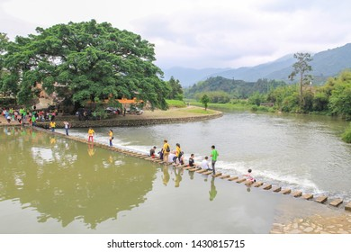 12/5/2012: tourists visiting Stepping Stone Bridge (stepstones) near Fujian Tulou, China (sets of stones arranged to form a simple bridge or causeway that allows a pedestrian to cross a river)