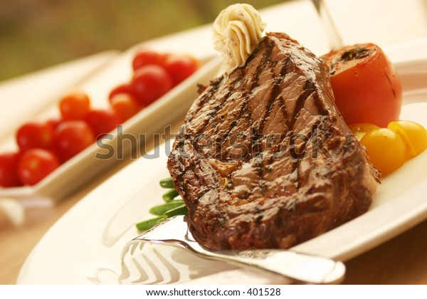 12oz ribeye steak topped with truffle butter and grilled tomato