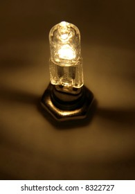A 12W halogen bulb in its mounting with a  brass nut.