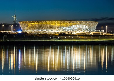 "13 April, 2018 Volgograd, Russia. New football stadium Volgograd Arena illuminated in the night, view from the left side of the Volga river. The monument ""The Motherland calls"" is standing to the left"