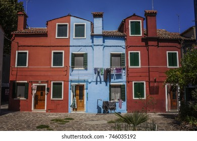 13 AUGUST, 2017: Burano Islands Venice, Colorful houses alongside the canal with boats at a bright summer day