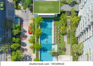 13 FEBRUARY 2017 - THAILAND, BANGKOK - Aerial View of a Swimming Pool with chilling man at the downtown, deck chair, and green trees around.