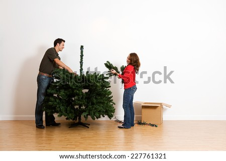 13 Image Series Of A Couple Assembling An Artificial Christmas Tree