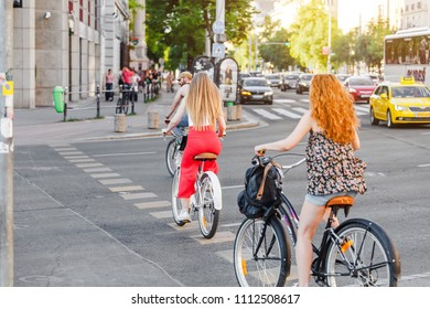13 MAY 2018, BUDAPEST, HUNGARY: pedestrian and cyclist crossing a busy city street crossroad