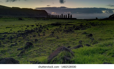 13 moai in Ahu Tongariki, Easter Island, at dawn. Mysterious monoliths enclosed between a green lawn and the blue ocean behind them.