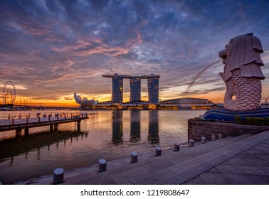 13 November 2014: Singapore - The skyline at sunrise, with the Merlion, the Marina Bay Sands, the Art and Science Museum and the Singapore Flyer, all under a dramatic sky.