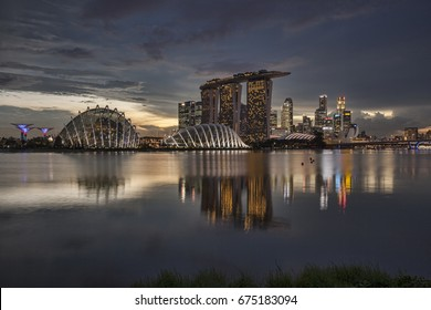 13 November 2014: Singapore - Singapore skyline reflected in Marina Bay, with Supertrees, the Cloud and Flower Domes, Marina Bay Sands and the Financial District, all under a moody twilight sky.