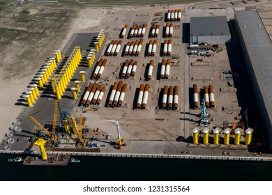 13 September 2018, Rotterdam, Holland. Aerial view of SIF Group at the Tweede Maasvlakte. Brown and white foundations for wind turbines and oil & gas platforms are stored at the dock.