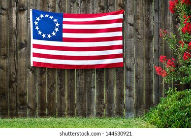 13 Star American flag, the Betsy Ross flag, displayed on rustic wooden fence