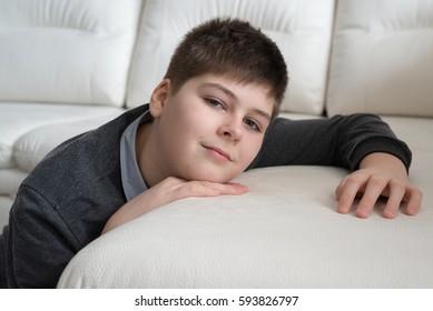 13 year boy sitting near the sofa in the room