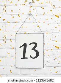13 years old birthday party card text with golden confetti, number thirteen, metal plate white brick background