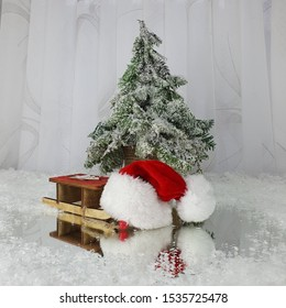 130 / 2048 Christmas tree covered with snow next to the sled, Santa's hat and Santa's cane on a white background and with reflected in the mirror.