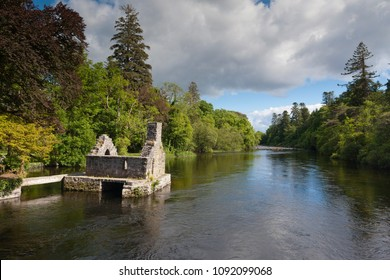 A 13th Century ruin on the Cong River, the Monk's Fishing House, part of Cong Abbey, set in a lush landscape with, in the distance, a weir across the river.  County Mayo, Ireland.