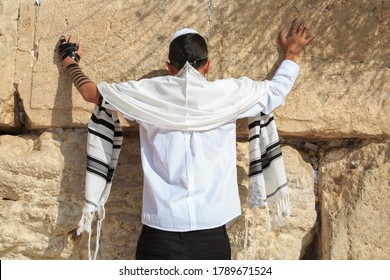 A 13-year-old teenager prays at the western wall. Bar mitzvah ritual