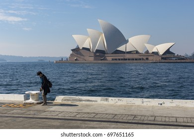 14 AUG 2017 - SYDNEY, AUSTRALIA - Sydney Opera House as seen from across the harbour with a lone man walking