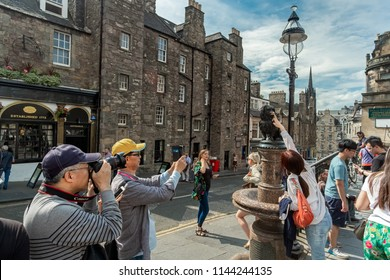 14. JULY 2018, EDINBURGH, UK - Turist with the satue of Greyfriars Bobby who became known in 19th-century for spending 14 years guarding the grave of his owner until he died himself.