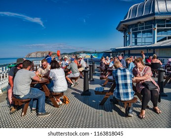 14 July 2018: Llandudno, Conwy, North Wales - People relaxing with drinks on a Saturday night at the end of Llandudno pier, during the continuing heatwave of summer.