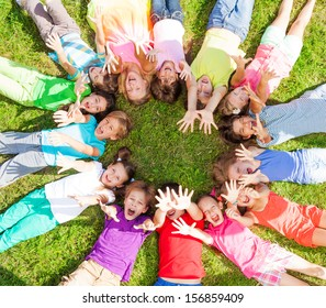 14 kids laying in a circle in the grass with happy faces shoot from above lifting hands above