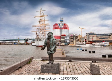 14 September 2018: Gothenburg, Sweden - Sculpture of Evert Taube in the Lilla Bommen district. Behind is the four masted barque Viking, and the Lilla Bommen building, known as the Lipstick.