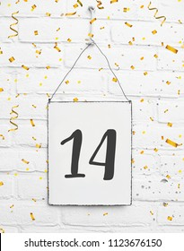 14 years old birthday party card text with golden confetti, number fourteen, metal plate white brick background
