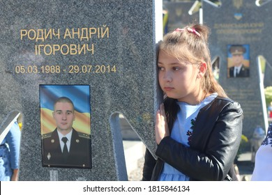 14.10.2018. Lviv, Lviv Oblast, Ukraine. The daughter of a Ukrainian soldier who died in the war between Ukraine and Russia hugs her father's grave in Lychakiv Cemetery in Lviv