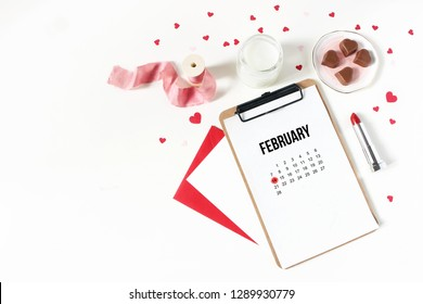 14th February, Valentines day still life composition. Candle, paper hearts confetti, chocolate, lipstick, gift ribbon and calendar isolated on white table background. Love concept. Flat lay, top view.