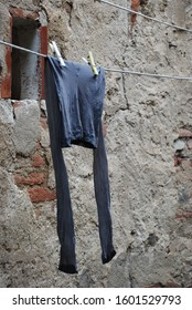 14th of July 2009 - Scene from Italian city with close up of a pair if leggings hanging in front of a textured wall, Cortona, Italy