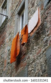 14th of July 2009 - Scene from Italian city with close up of hanging laundry in front of a textured wall, Cortona, Italy