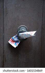 14th of July 2009 - Scene from Italian city with close up of a leaflet put into a knocker on a brown textured door, Cortona, Italy