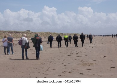 14th May 2017- Visitors walking along a sandy beach to a motorcycle speed event at Pendine, Carmarthenshire, Wales, UK.