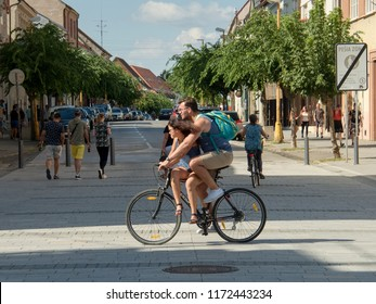 15 August 2018, Trnava, Slovakia A young man takes a girl in the top tube of his bicycle frame. The girl is sitting behind her hair in the wind,
