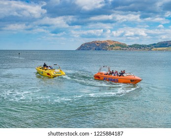 15 July 2018: Llandudno, Conwy, UK - Jet boat rides in the bay, with the Little Orme in the background.