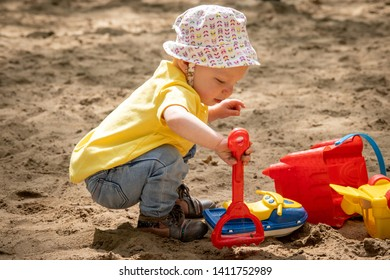 15 month old adorable blond caucasian toddler playing on sand box at the public park outdoor Sorel-Tracy Quebec Canada playing on sand box at the public park outdoor Sorel-Tracy Quebec Canada