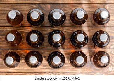 15 neatly aligned rows of bottled craft beer capped with bottle tops viewed top down on a wooden table