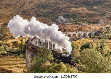15 October 2015: Highland, Scotland, UK  - The Jacobite steam train blows steam as it crosses the Glenfinnan Viaduct.
