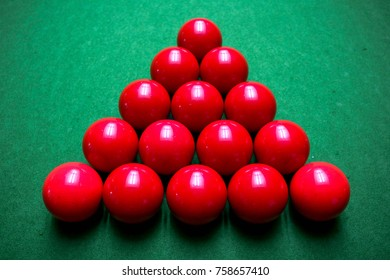 15 red snooker balls arranged in a triangle on a green snooker table.