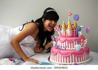 A 15 year old hispanic girl celebrates her birthday with a fancy birthday cake with a candyland theme. The three layer cake is covered with fondant and candy decorations.