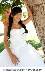 A 15 year old hispanic girl celebrates her birthday with a tiara and fancy white dress