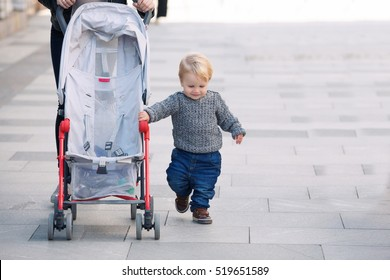 1,5 year-old independent baby walking with Mother and baby carriage. Toddler rolls stroller himself outdoors