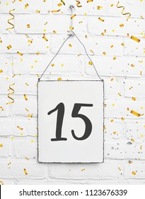 15 years old birthday party card text with golden confetti, number fifteen, metal plate white brick background
