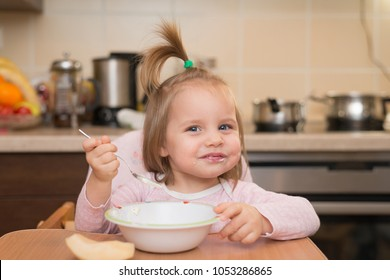 1,5 years old girl eating by herself