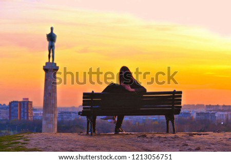 15.04.2018. a kiss of lovely couple on the bench on colorful orange urban sunset with cityscape in background in Belgrade, Serbia