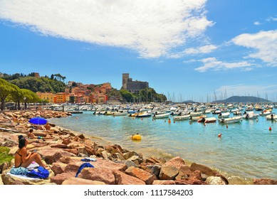 15.07.2017.beach scene with colorful boats and seascape with old castle and blue cloudy in Lerici in Liguria, Italy