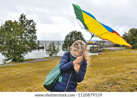 15.08.2016. Young woman fighting against wind with colorful umbrella on desert beach in Estonian capital Tallin, Estonia