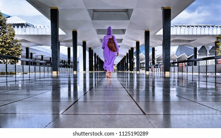 15.08.2017. Kuala Lumpur Malaysia. A young women with traditional local clothes walking between black marm columns inside national mosque in Kuala Lumpur