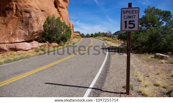 A 15-mph speed limit on desert road with red-rock cliffs in the Colorado National Monument.