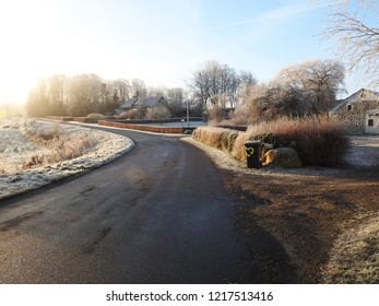 15th of December 2016 - Scene from a frosty Danish country road with view past bushes and a recycling bin to a a couple of houses, Gultentorp, Aalborg, Denmark