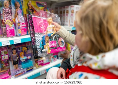 15th - December -2019 - Stoke on Trent, Staffordshire, A cute little toddler girl looks at a Barbie in a wheelchair on sale at the Entertainer toy shop, disabled Barbie doll