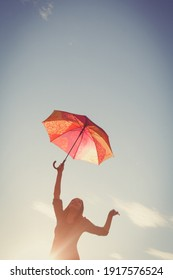 The 15-year-old girl dances with an umbrella in her hands against the clear sky, the picture is tinted in retro colors and a vignette is added