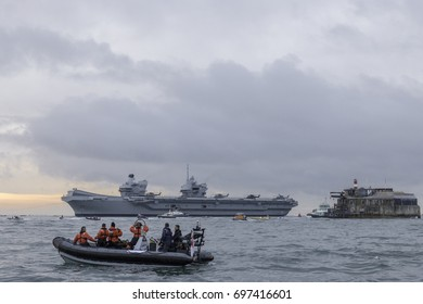 16 August 2017, English Channel Approaching Portsmouth, England; The Aircraft Carrier HMS Queen Elizabeth approaching her home port of Portsmouth for the first time. The sun is rising behind her.